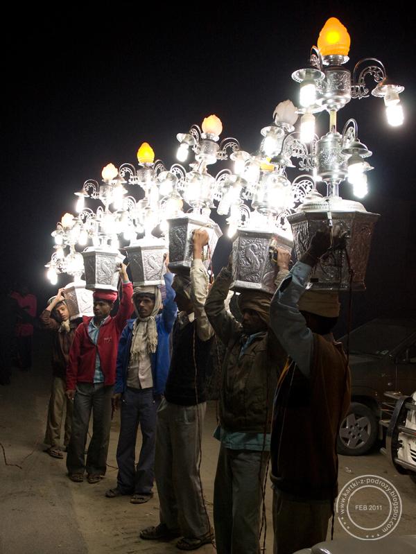 Mężczyźni oświetlają drogę.