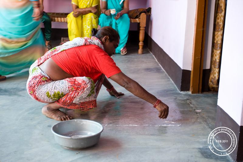 Kobieta przygotowuje miejsce obrządku oczyszczania / Womam is preparing a place for the purifying rite