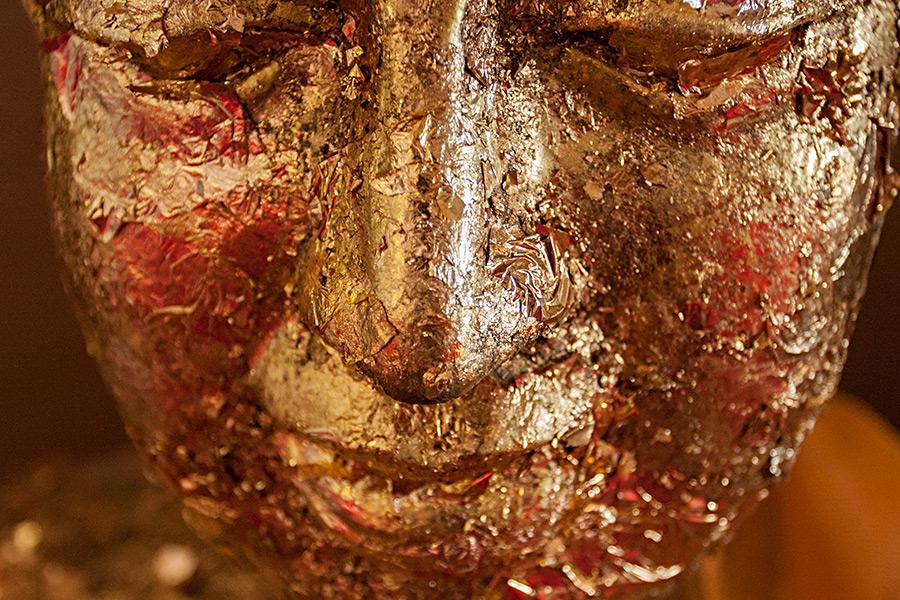 Oblepianie głowy Buddy płatkami złota przez wiernych jest typowym obrządkiem w tej religii.