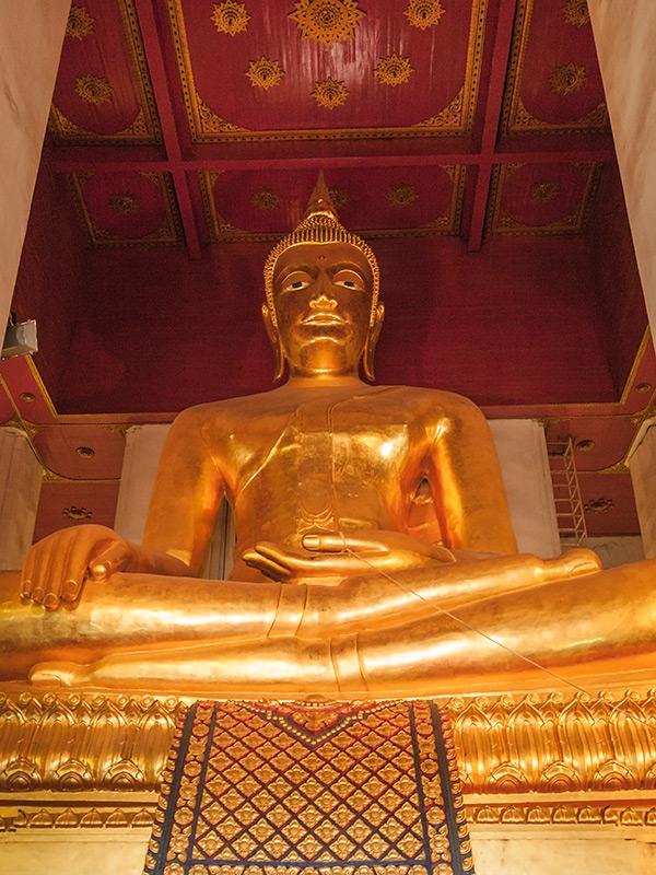 Wizerunek Buddy charakterystyczny dla północnej Tajlandii. Mnisi buddyjscy podczas modlitwy często są połączeni ze sobą sznurkiem. Tutaj kciuk Buddy też jest obwiązany sznurkiem.