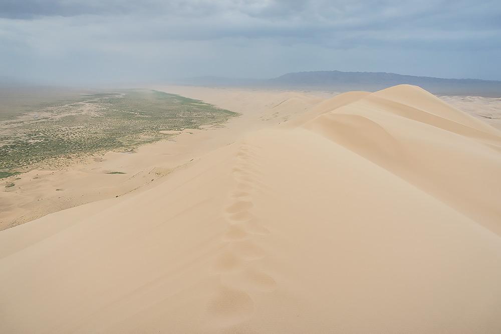 Suchy piasek smagany przez rozpędzony na pustkowiach wiatr.