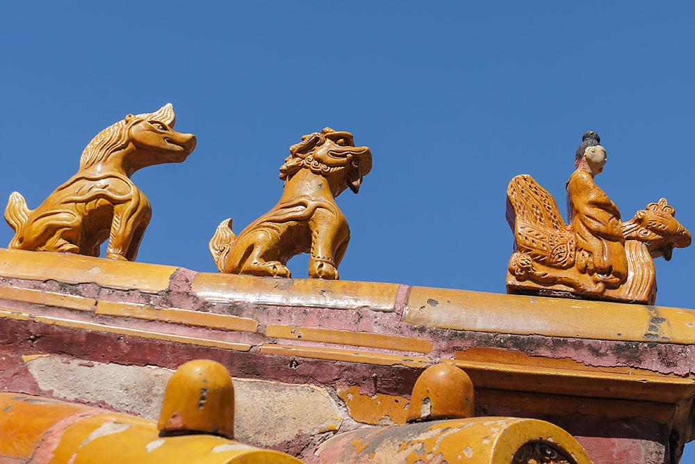 Figury zdobiące dachy oficjalnych budynków - mityczne bestie podążają za mężczyzną dosiadającym feniksa.